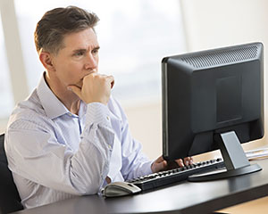 Businessman Working On Desktop Pc In Office